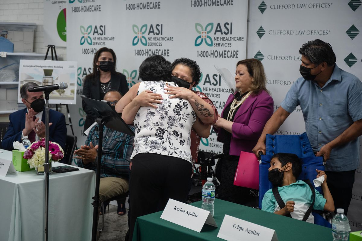 Itza Pantoja, in pink, hugs Karina Aguilar at ASI Chicago in Logan Square where the Pantoja family donated their son Dylan's medical equipment to Felipe Aguilar, who has cerebral palsy.