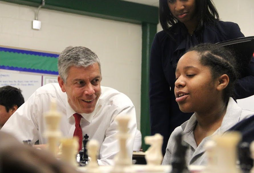 Arne Duncan talks about strategies for chess with a student learning through play at Douglass K-8 Optional School.