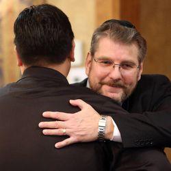 Utah Attorney General Sean D. Reyes hugs Alan Bachman at the annual Interfaith Prayer Breakfast at the Hellenic Cultural Center in Salt Lake City on Thursday, Feb. 5, 2015.