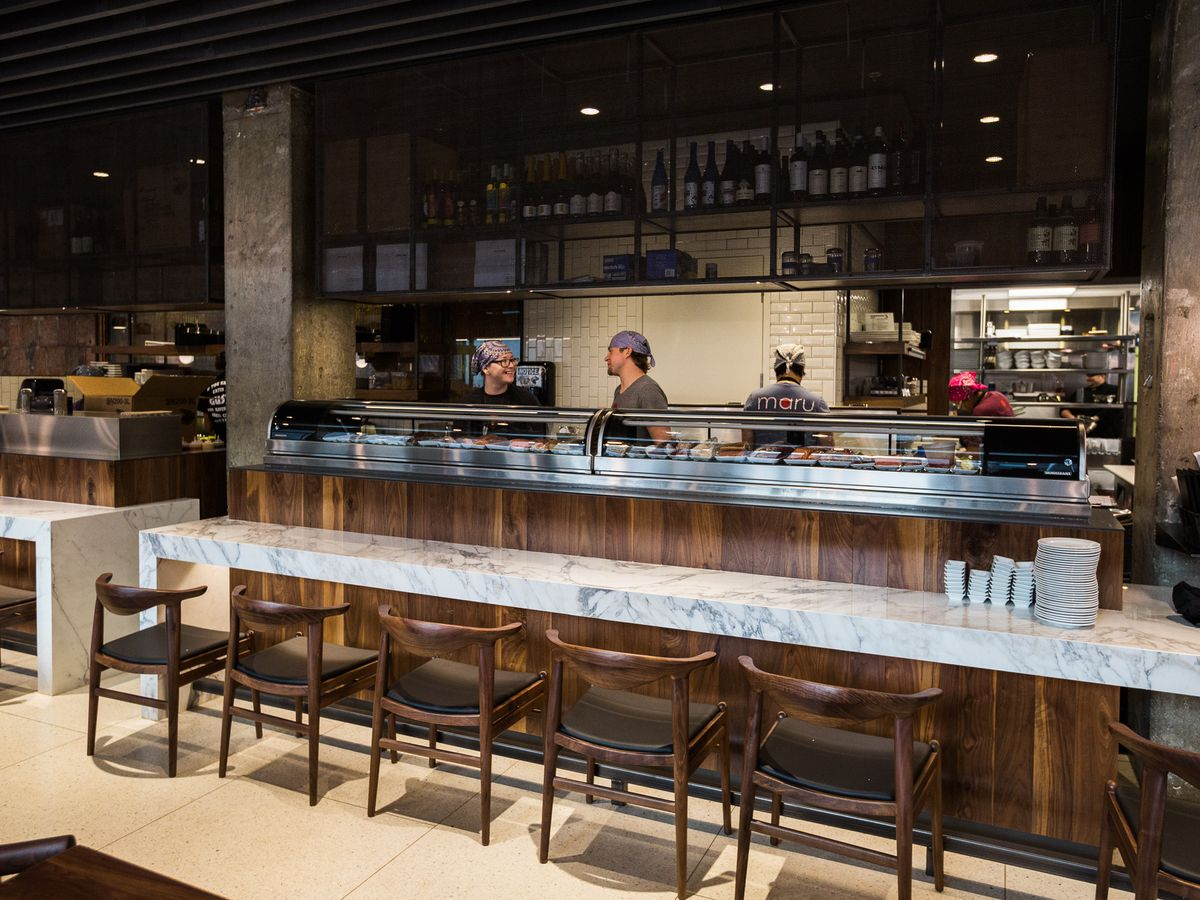 a marble sushi counter with wood chairs at maru sushi