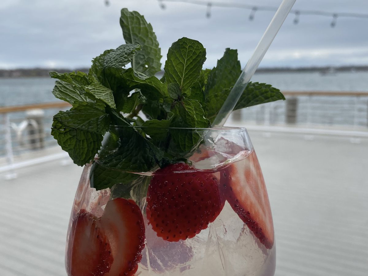 A clear cocktail in a wine glass is topped with sliced strawberries and a few sprigs of mint, overlooking the water.