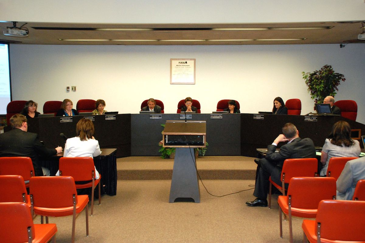 Eight people sit on a dais behind a panel, with about six people in orange chairs in the audience.
