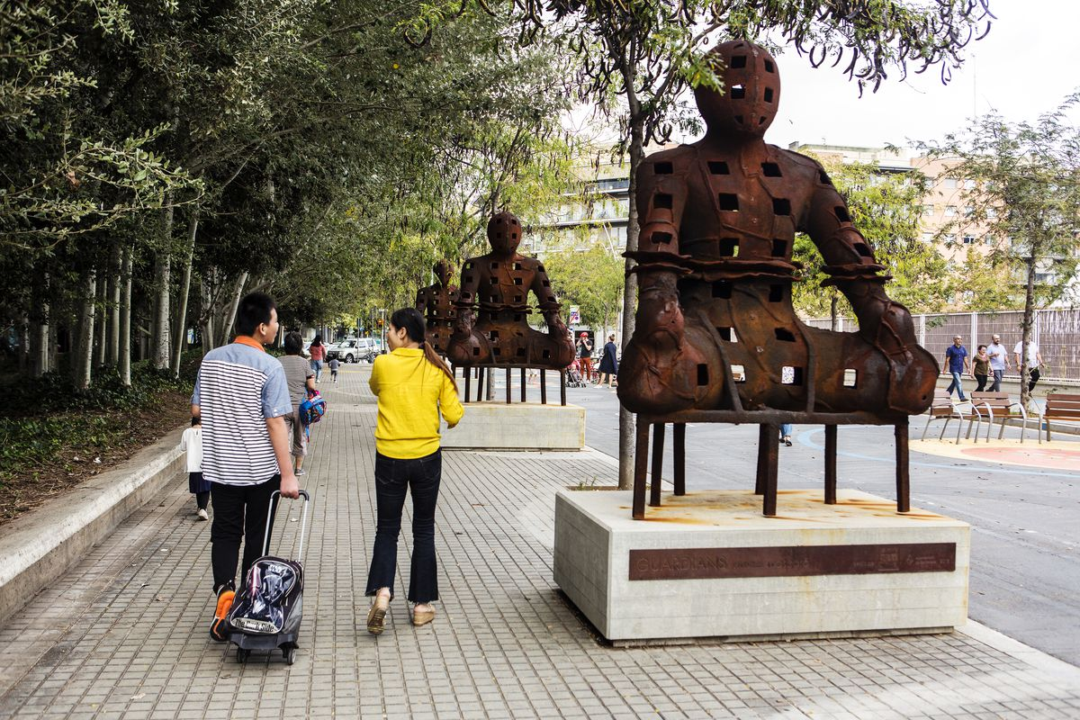"""Parents walk next to the """"protective statues of the superblock"""" after picking up their children from a nearby school in the Poblenou district."""