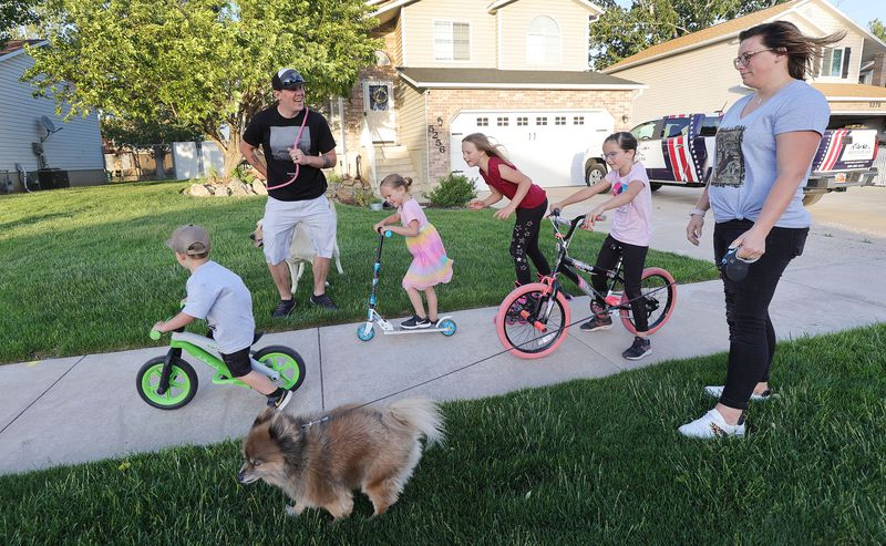 Tyler and Stephanie Parkin walk and bike with their children near their home in Roy on Thursday, May 20, 2021. The Parkins say they severely limit screen use by their children.