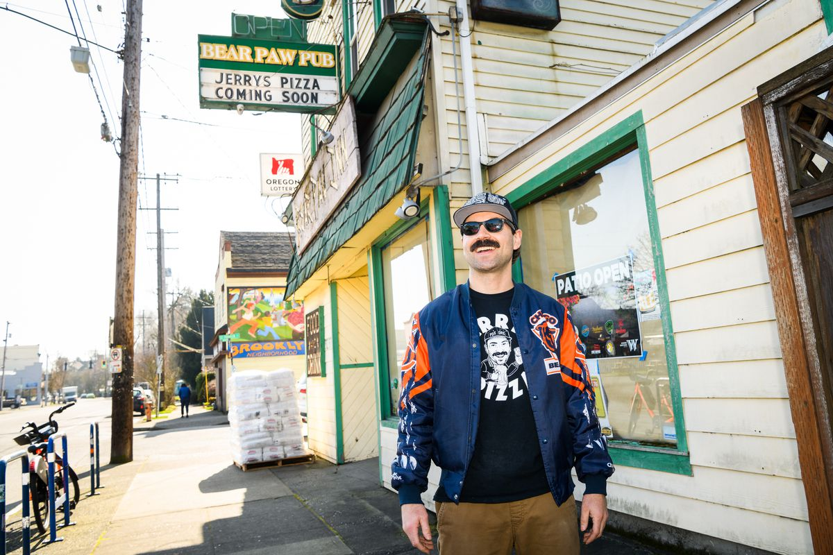 Jerry Benedetto of Jerry's Pizza — a man with a black handlebar moustache, a Chicago Bears letterman's jacket, and a baseball cap — stands outside the Bear Paw Inn.