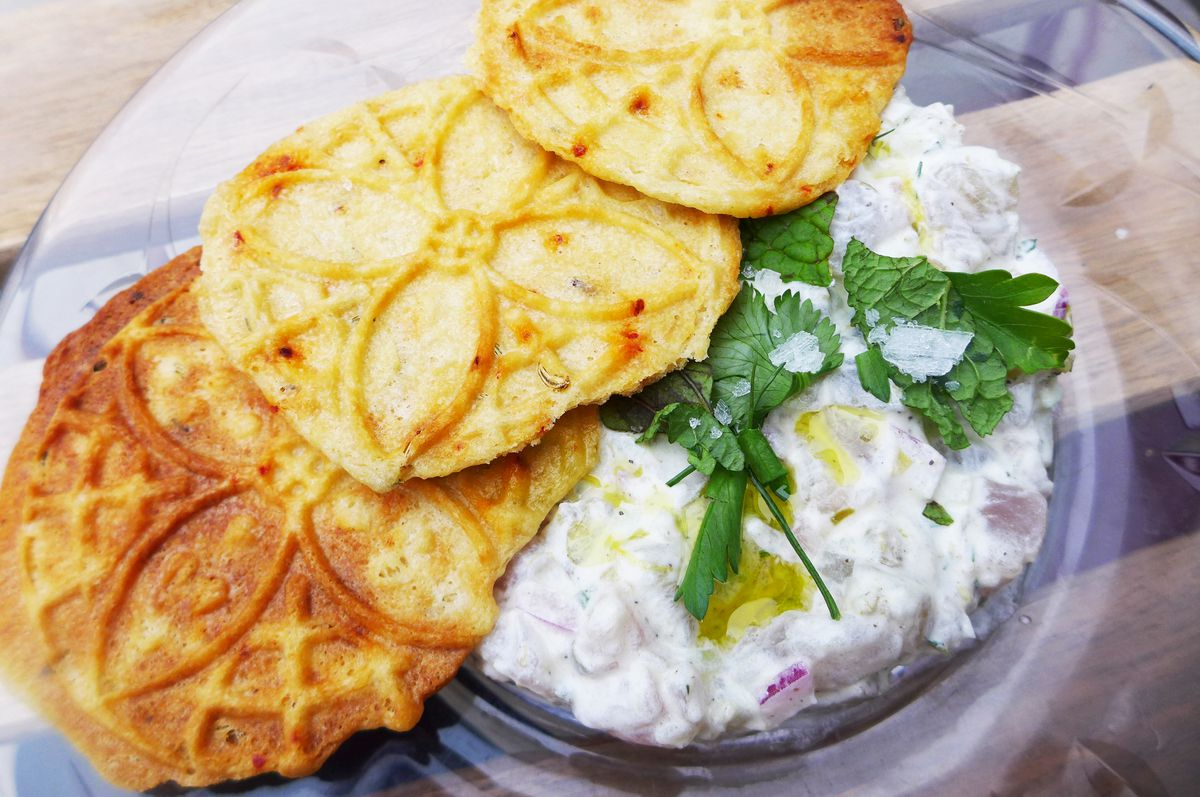A plate of diced raw fish in creamy sauce topped with three cookies.
