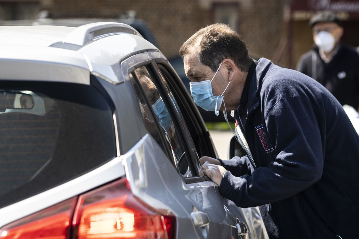 """U.S. Rep. Jesus """"Chuy"""" Garcia approaches a vehicle to give out free blue surgical masks and hand sanitizer in Little Village on the Southwest Side, a neighborhood hit hard by the coronavirus pandemic, Wednesday morning, May 13, 2020."""