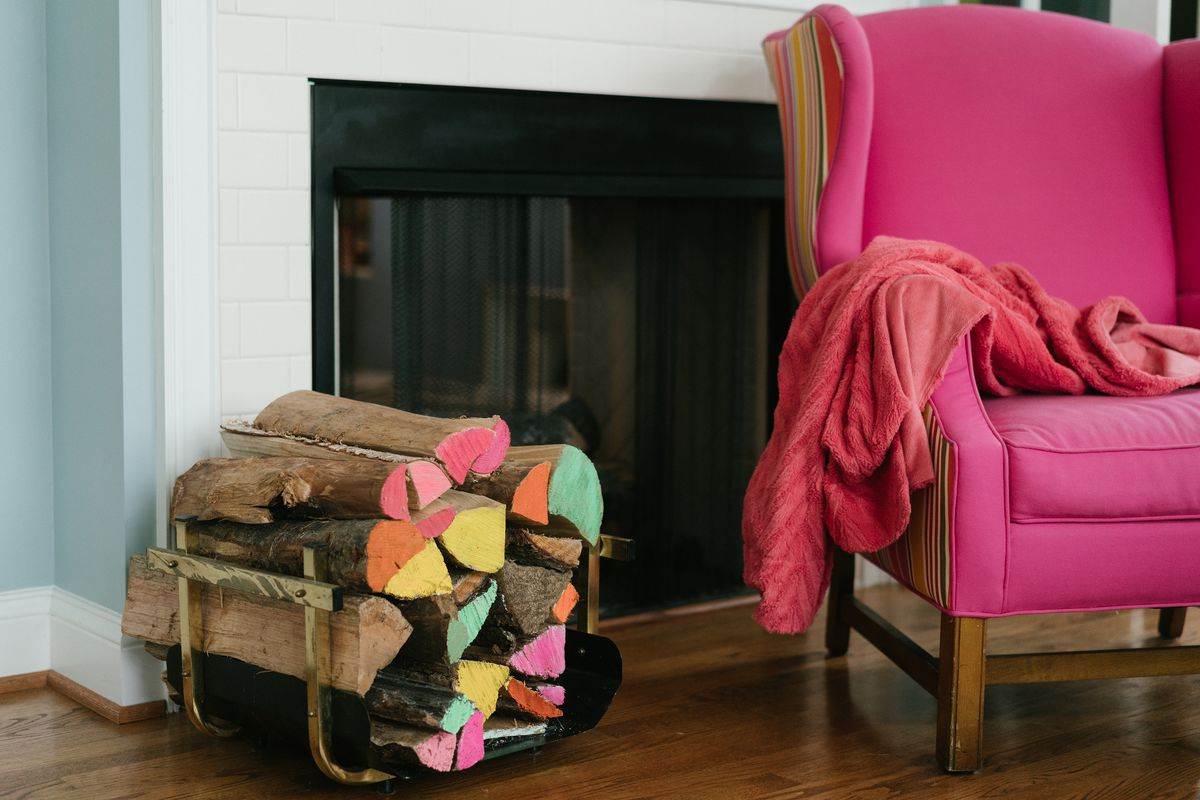 A pink chair and firewood with pink, yellow, green and orange on the ends.