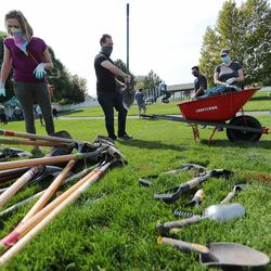 Volunteers pick up their tools as they take part in a Tree Utah community planting event at Sommerset Park in Lehi on Wednesday, Sept. 23, 2020.