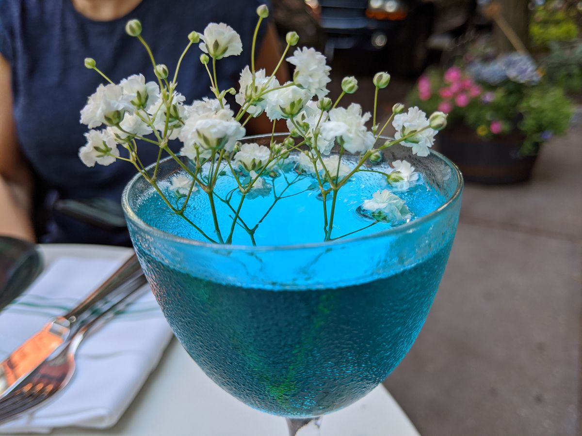 A blue cocktail with a sprig of flowers absurdly sticking out the top.