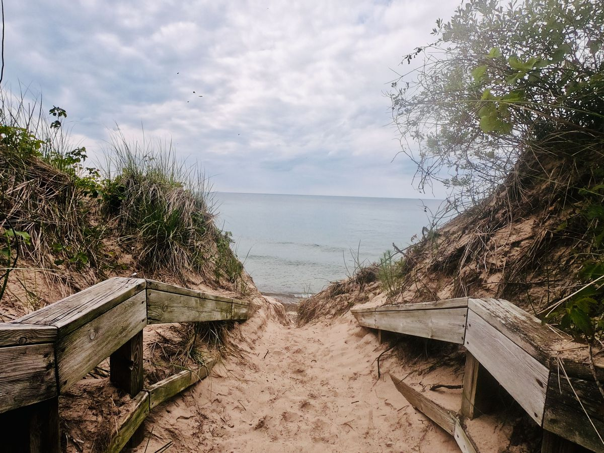 A sandy walkway with wooden banisters leading to Lake Michigan shoreline and a cloudy sky.