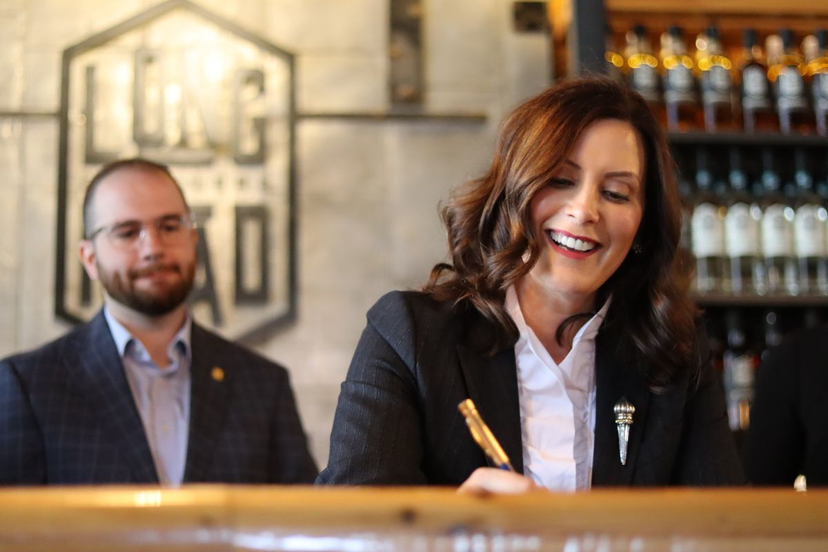 Gov. Gretchen Whitmer smiles and she signs paperwork. There's a man and a sign for Long Road Distillers in the background.