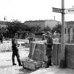 Two East German border guards observe the construction of the concrete wall August 23, 1961 at the sector border Heidelberger street - Wildenbruch street, in the district of Neukoelln in Berlin, Germany.