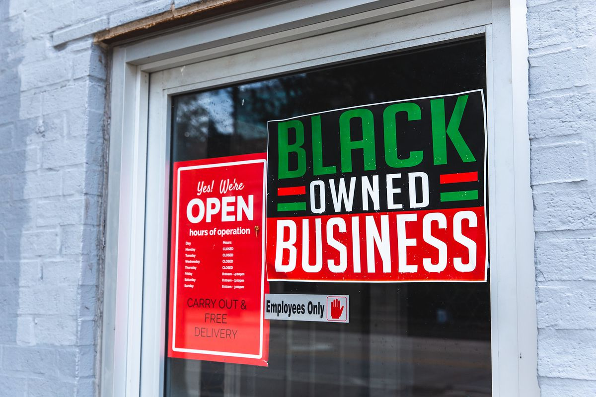 """A glass door with a sign """"black-owned business"""""""