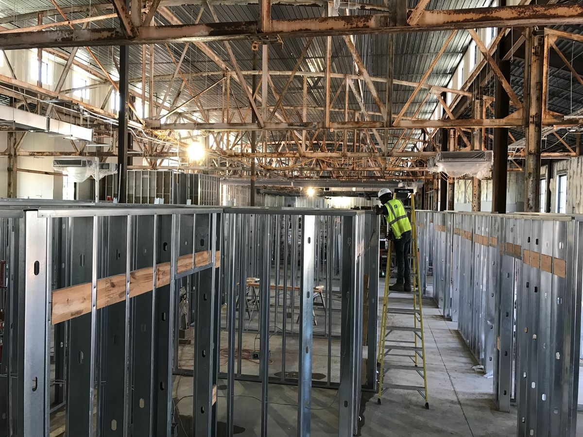 A picture of the interior of an old building with new metal framing inside.