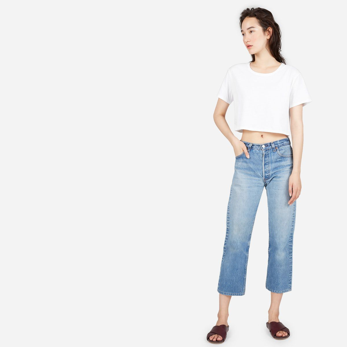 A model in a white cropped T-shirt and jeans