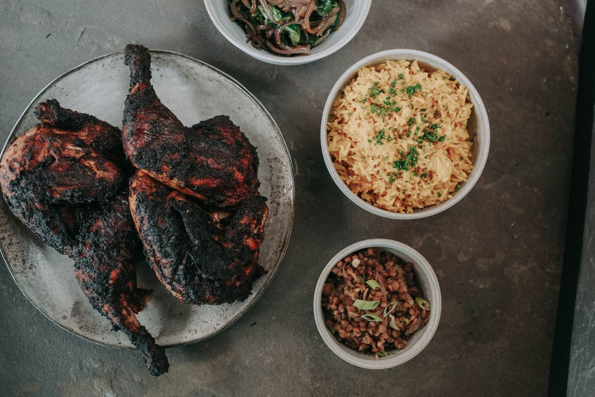 A plate of grilled chicken with berbere spices next to a bowl of rice and other sides