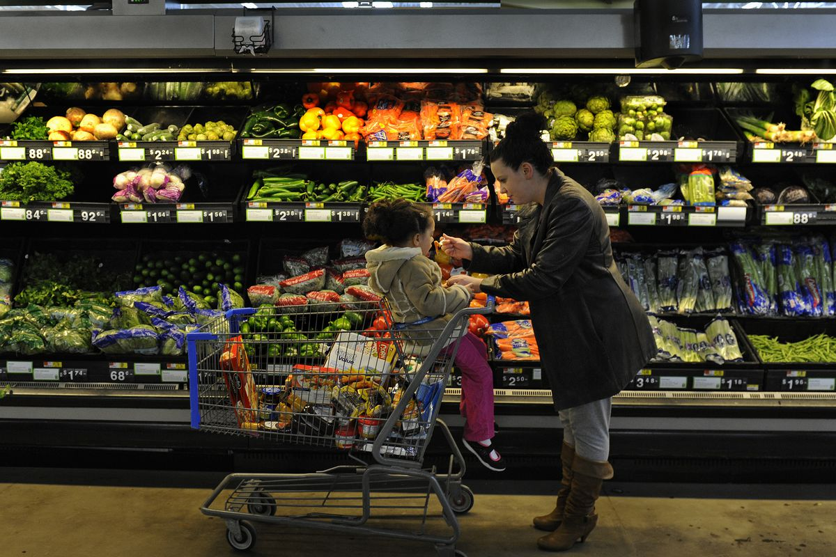 A woman pushes a grocery cart with a child in the seat down the vegetable aisle of a grocery store.