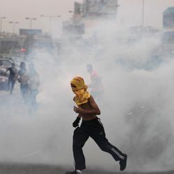 Anti-government protesters run through tear gas fired by riot police Friday, April 20, 2012, to prevent them from marching toward the hub of last spring's pro-democracy uprising at the end of a mass rally just outside Manama, Bahrain. Tens of thousands of anti-government protesters flooded a major highway in Bahrain demanding a halt to the Formula One race on its first day of practice runs, as the Gulf kingdom's crown prince vowed the country's premier prestige sporting event would go ahead.