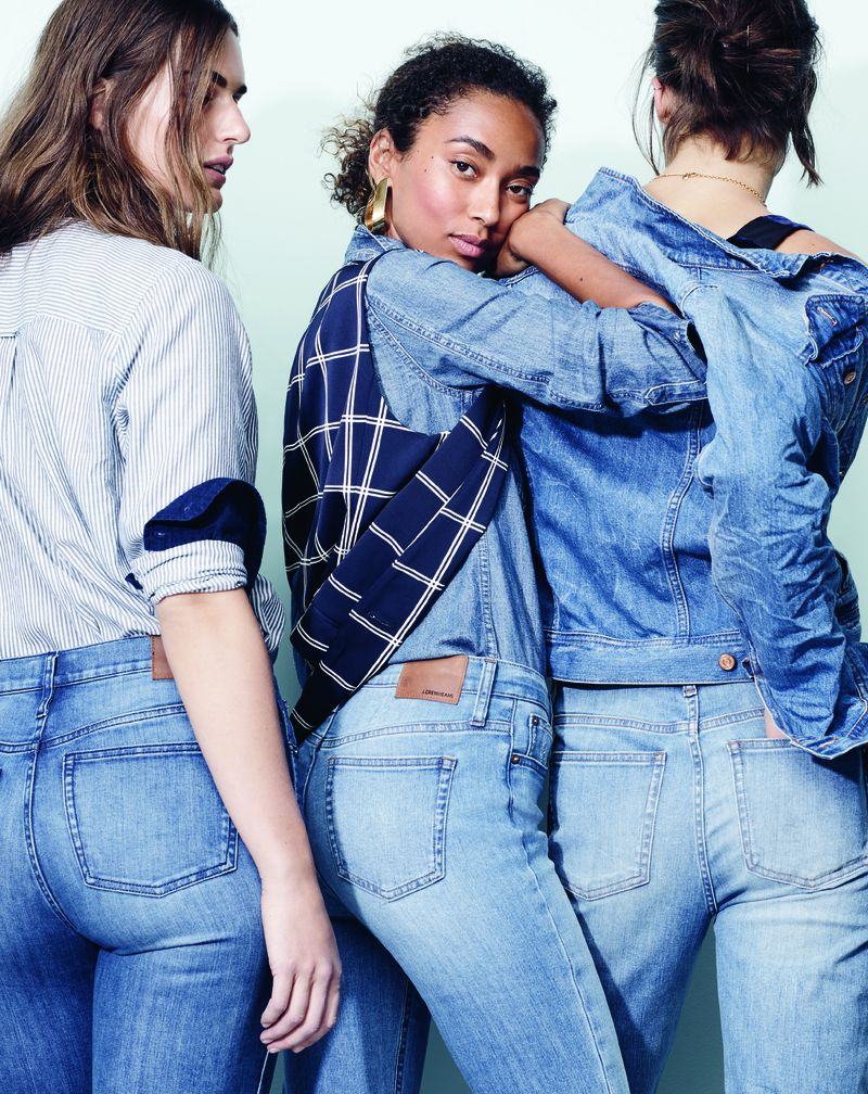 Three women wear jeans and denim shirts.