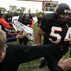 Monticello's Siali Huavi runs onto the field as fans line the end zone.