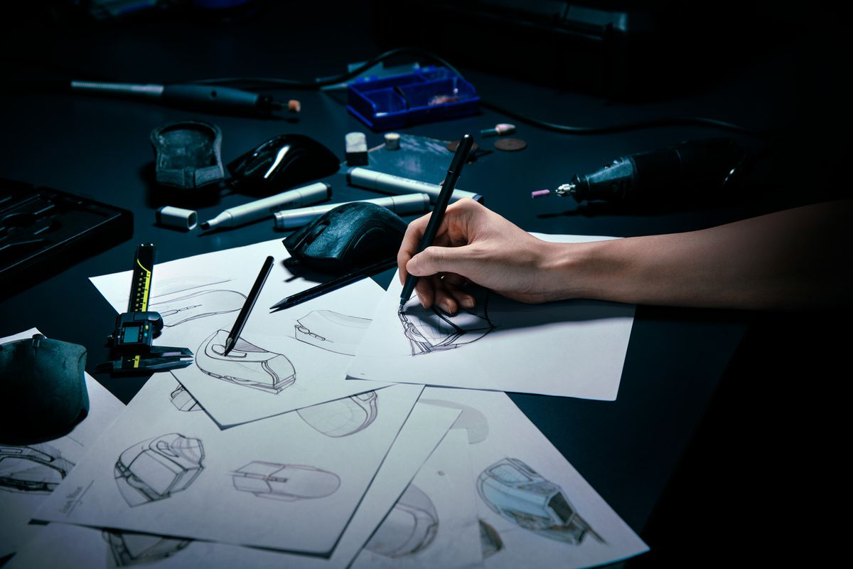 A photo of a hand drawing a bunch of designs of computer mice.