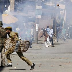 """Kashmiri Muslim protesters throw stones at Indian policemen during a protest in Srinagar, India, Friday, Sept. 14, 2012. The protest was held against an anti-Islam film called """"Innocence of Muslims"""" that ridicules Islam's Prophet Muhammad."""
