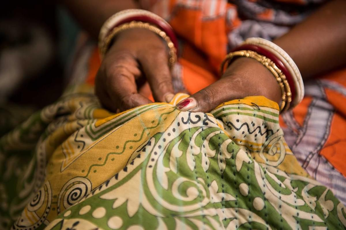 An artisan sews a Sari Bari blanket in Calcutta.
