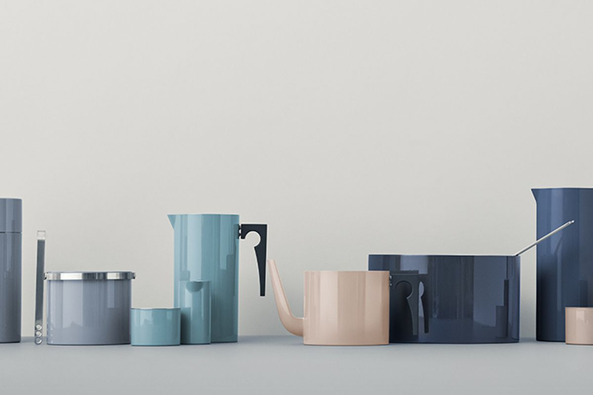 Array of pastel-hued serveware like cylindrical coffe pots, teapots, salad bowls, and cups lined up in front of grey backdrop.