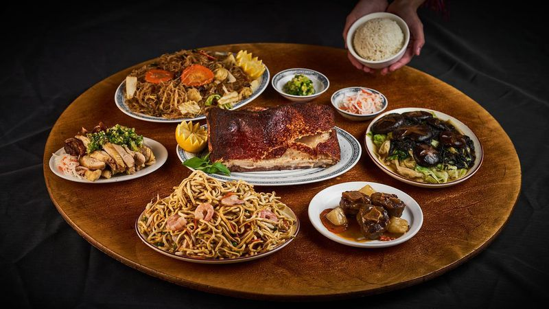 Eight dishes with roast pork at the center