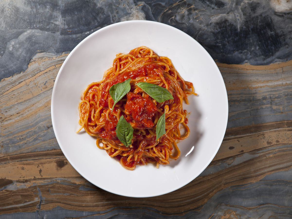 An overhead photograph of a bowl of spaghetti in red sauce on a white plate. A few sprigs of basil adorn the dish.