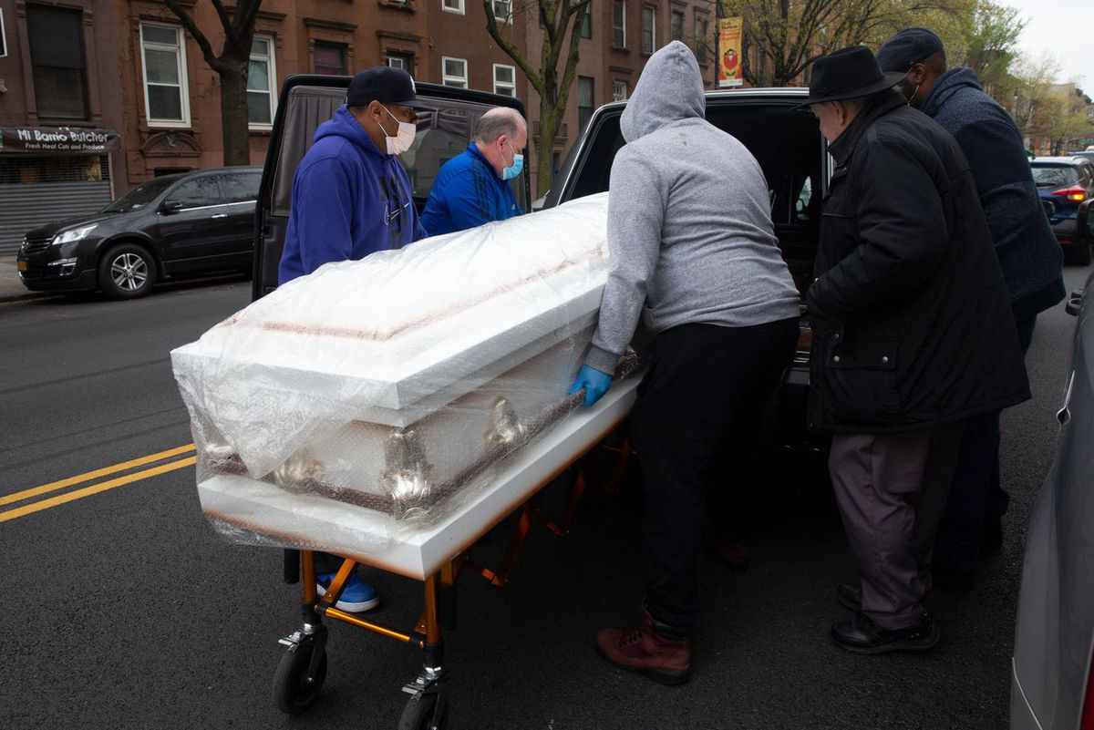 Workers at First Avenue Funeral Services in East Harlem bring a casket out to a hearse during the coronavirus epidemic.