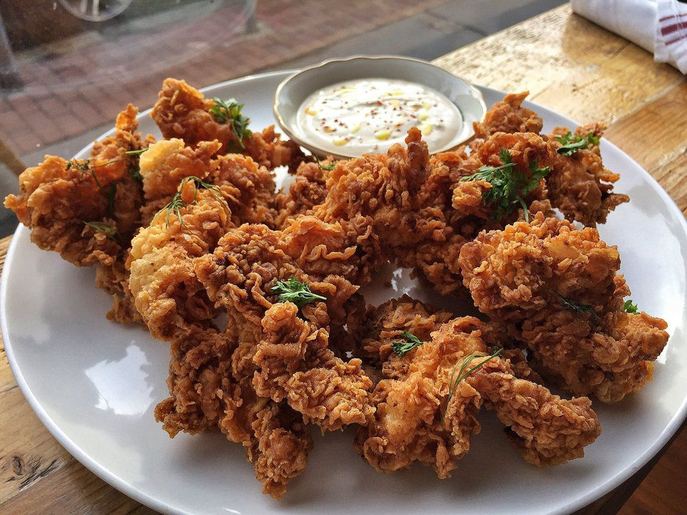 Pieces of crispy fried chicken sit on a white plate on a wooden table next to a window.