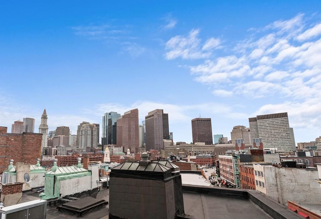 The view of a cityscape and skyline from a roof deck.
