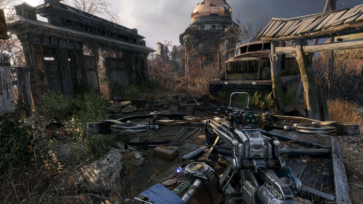 This screenshot from Metro Exodus shows the character, from a first-person perspective, exploring a village full of wrecked buildings and debris. He hold a crossbow in front of him.