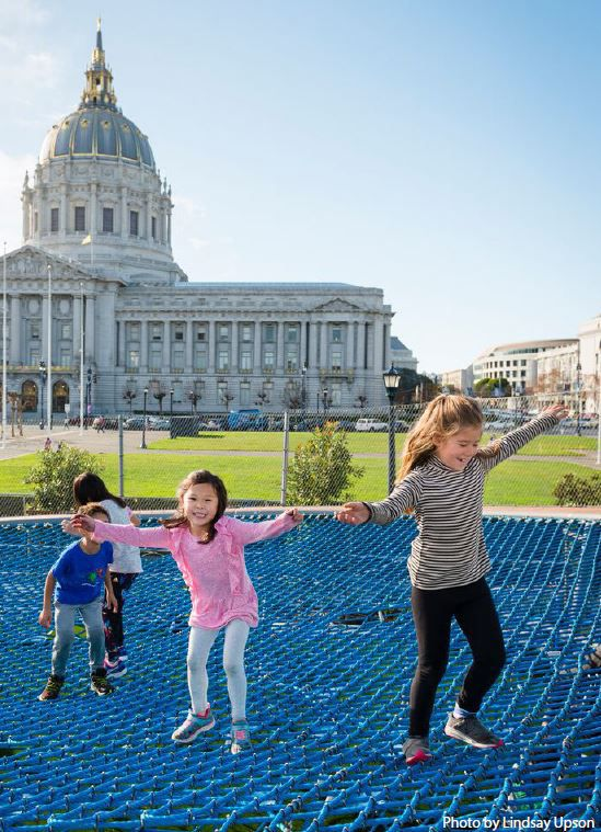 Happy kids bouncing on a trampoline-like net in front of SF City Hall.