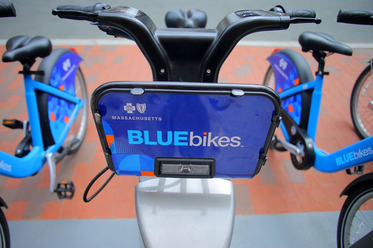 A bicycle which is painted blue. There is a sign that reads Massachusetts and BlueBikes that is sitting between the bicycle's handlebars.
