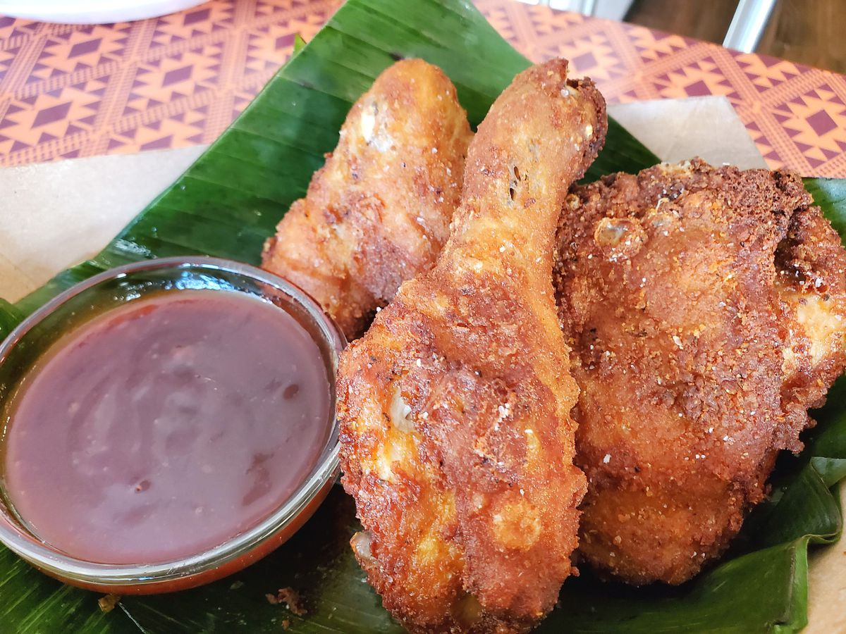 Three pieces of Thamee's Burmese Fried Chicken and a side of deep red mumbo sauce rest on a green banana leaf