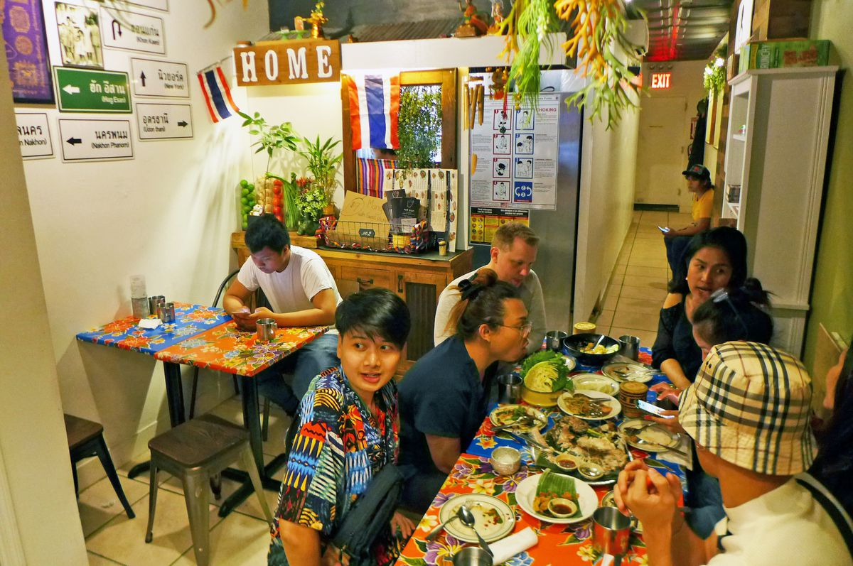 Hug Esan's small dining room has colorful red and blue floral tabletops. Many diners sit with a table full of dishes