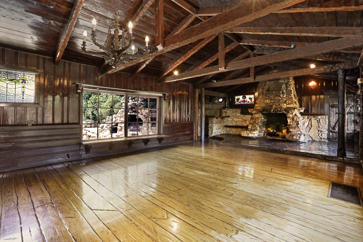 Large room with wood floors, exposed beams, and a stone fireplace.