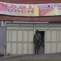 Kenyan paramilitary personnel guard the church door after a hand grenade attack on a church in downtown Nairobi, Kenya, Sunday, April 29, 2012, where 1 person died and more than a dozen were injured.  The incident is the latest in a string of grenade attacks since Kenya sent troops into Somalia in October last year.