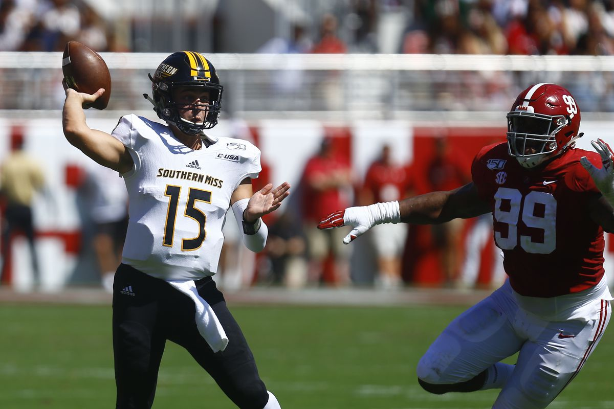 Southern Miss Golden Eagles quarterback Jack Abraham throws a pass as Alabama Crimson Tide defensive lineman Raekwon Davis pursues during the first half of an NCAA college football game at Bryant-Denny Stadium.
