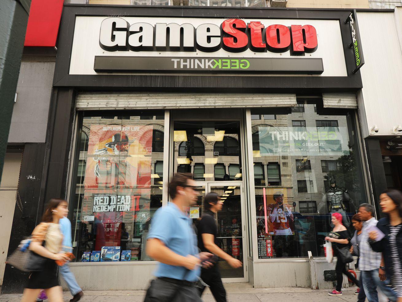 People walking by a GameStop.