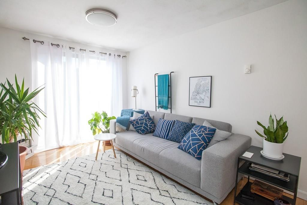 A small living room with a couch and a long window with the curtains drawn.