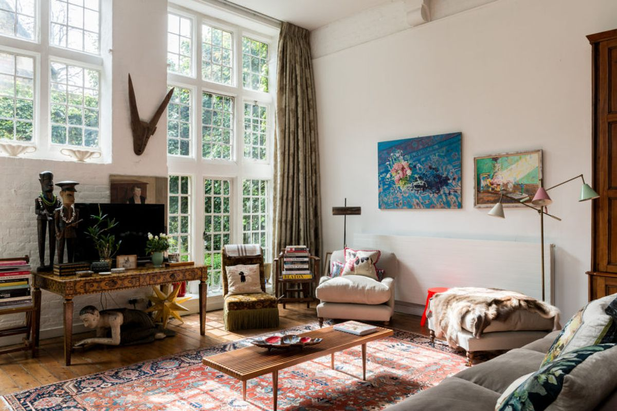 Interior shot of white-walled double-height living space with a wall of paned windows/