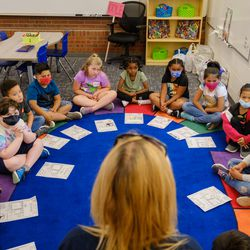 A teacher leads an exercise with her students, who completed worksheets about themselves. This year, students in Aurora Public Schools can attend school in-person five days a week, fully online, or in a flex model.