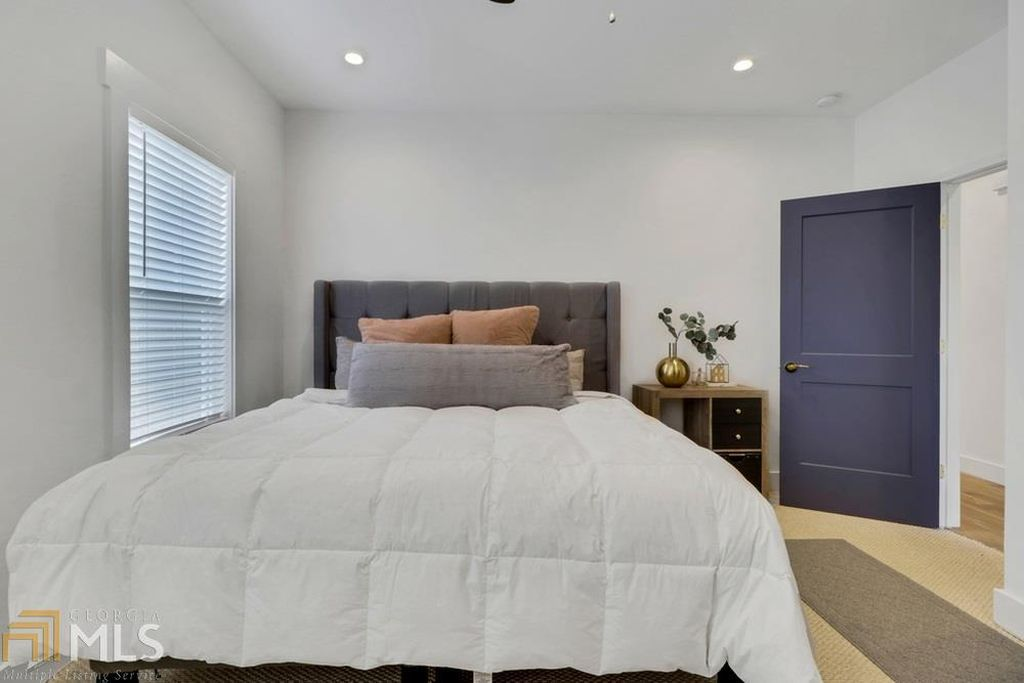 a large white bedroom with a big white bed.