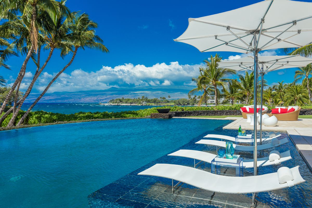 An outdoor pool has ocean and palm tree views, with white lounge chairs and umbrellas in the pool.