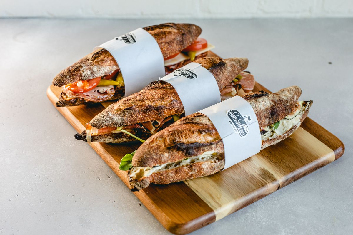 A wooden tray holding three sandwiches on bagettes.