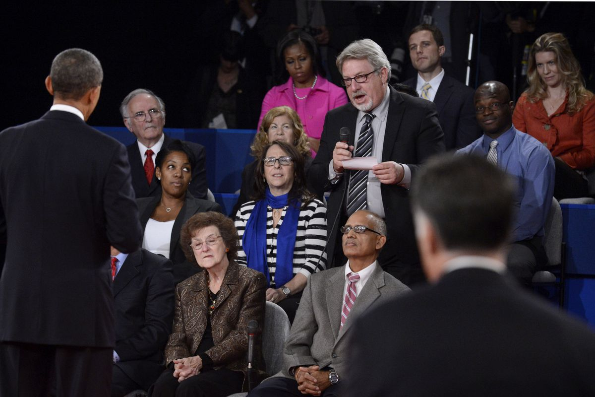 President Barack Obama answers a question from an audience member during a town hall–style debate at Hofstra University October 16, 2012, in Hempstead, New York.